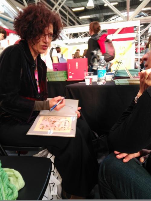 """Chiara Carrer, nello stand della Kalandraka dedica una copia di """"E' non è"""" a una lettrice."""